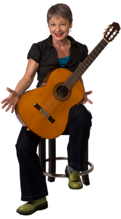 Photo of Sister Dorothy in casual wear sitting on stool with acoustic guitar